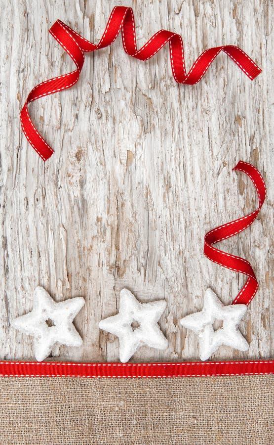 Decoración de la Navidad con las estrellas, la cinta y la arpillera de plata foto de archivo