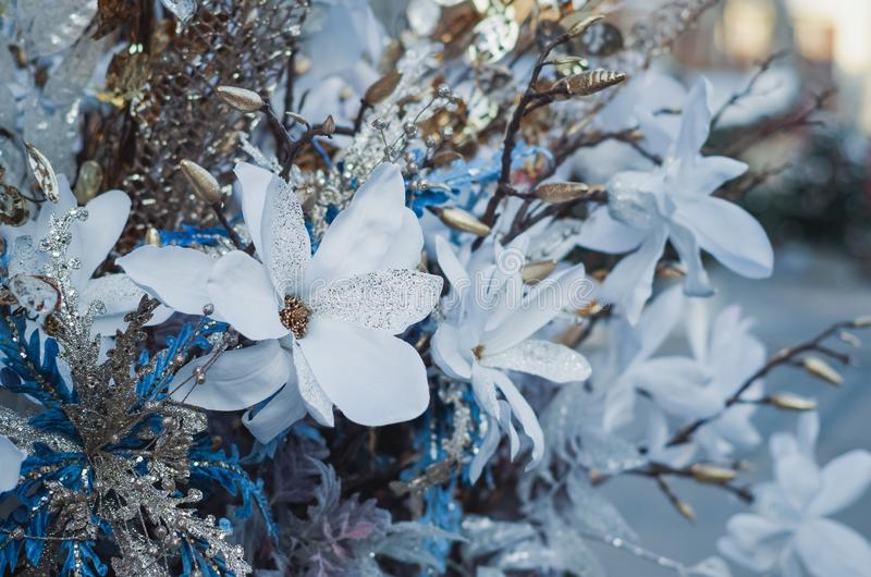 Decoración de la Navidad con las hojas blancas del flor, de bronce y las luces en la calle imágenes de archivo libres de regalías