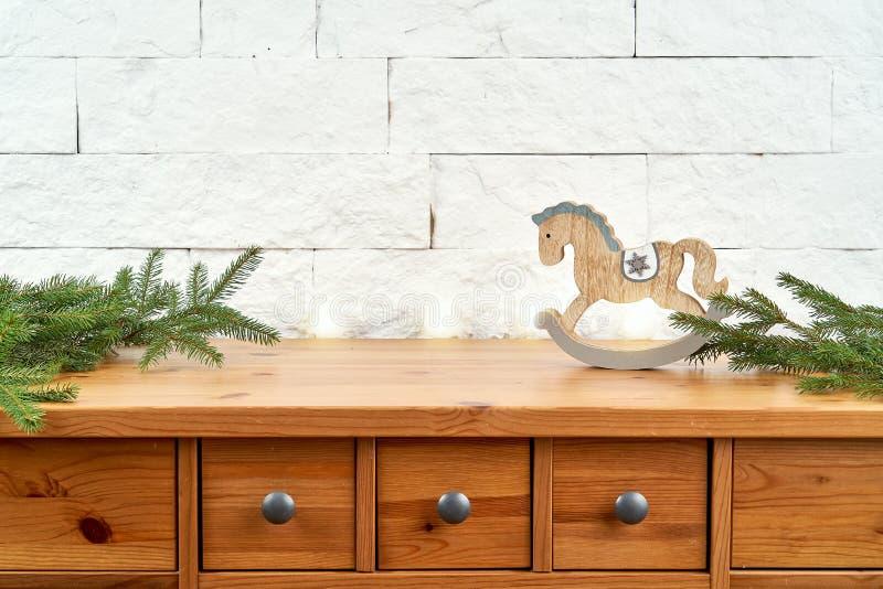 Decoración de la Navidad con las ramitas de la picea y del caballo en el estante en el fondo de una pared de ladrillo foto de archivo libre de regalías