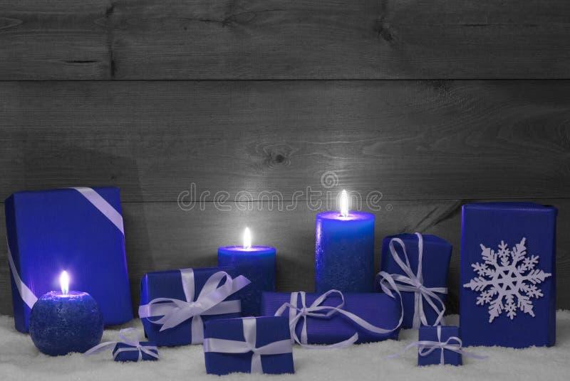 Decoración de la Navidad con las velas, los presentes y la nieve azules imagenes de archivo