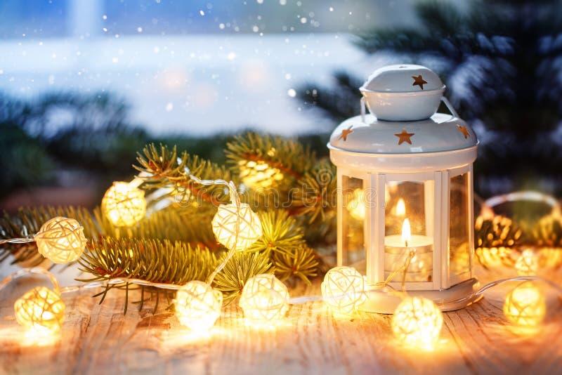 Decoración de la Navidad con la linterna blanca de la vela, las ramas de árbol de abeto y la guirnalda luminosa fotografía de archivo