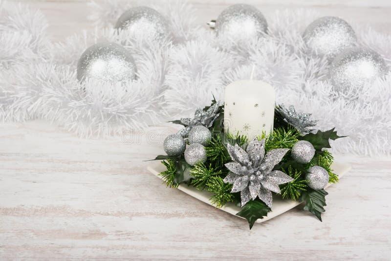 Decoración de la Navidad con la vela, la rama del abeto y las bolas de la plata en el fondo de madera blanco foto de archivo