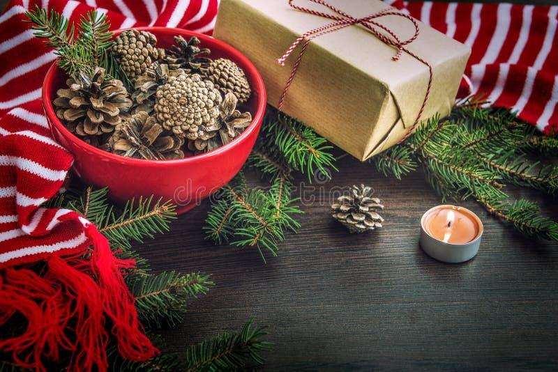 Decoración de la Navidad - cuenco rojo por completo de abeto-conos, de caja de regalo envuelta en el papel de Kraft, de ramas del imagen de archivo