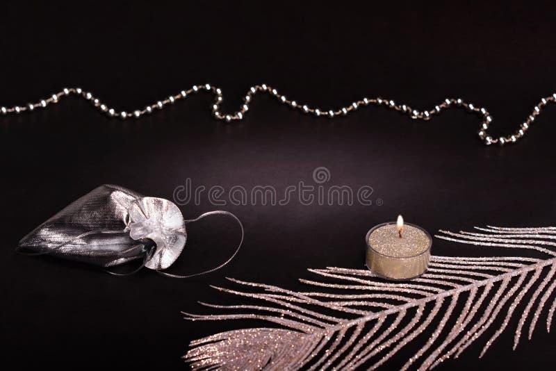 Decoración de la Navidad en fondo negro Vela, bolso de plata del regalo del lazo y pluma fotografía de archivo libre de regalías