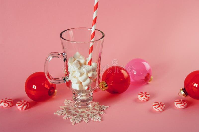 Decoración de la Navidad en fondo rosado Caramelo con los ornamentos de la Navidad La taza de cristal con el papel rayó la paja y fotos de archivo libres de regalías