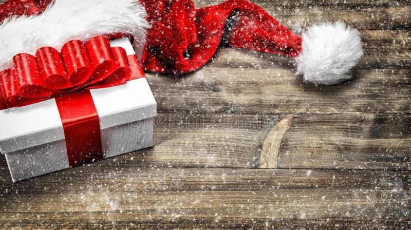 Decoración de la Navidad Nieve que cae del arco rojo de la cinta de la caja de regalo fotografía de archivo