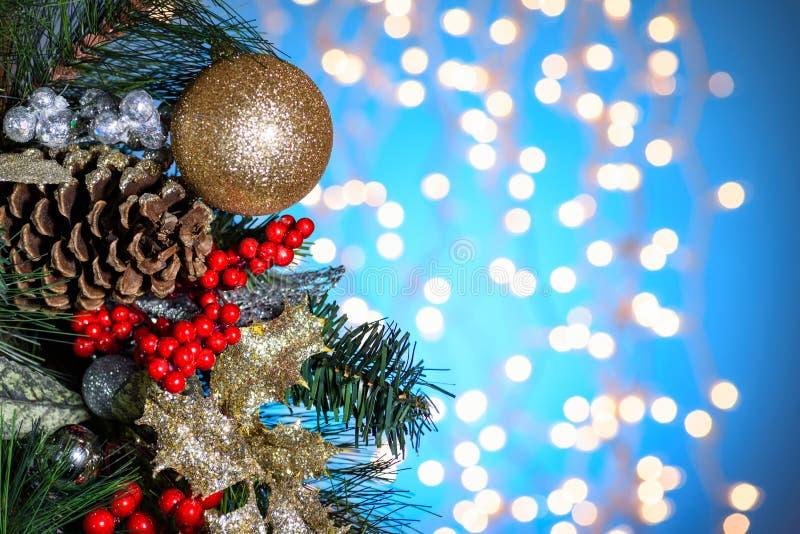 Decoración de la Navidad, ornamentos El abeto ramifica, las bayas del acebo, cono del pino, bola de oro en fondo azul claro Refle imagenes de archivo