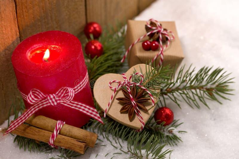 Decoración de la Navidad - vela y presentes lindos en la nieve imagen de archivo
