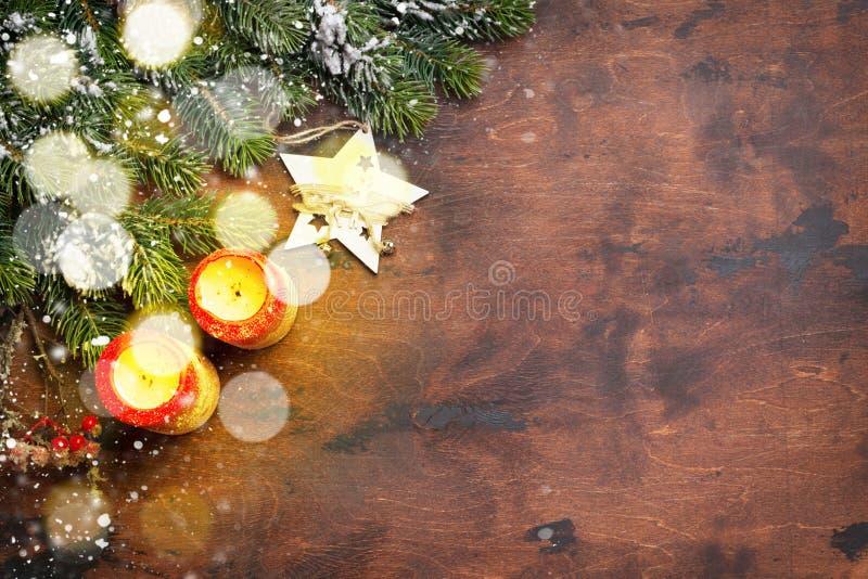 Decoración de la Navidad, velas y rama de árbol de abeto cubierta por la nieve en fondo de madera Contexto de Navidad de la visió imagen de archivo libre de regalías