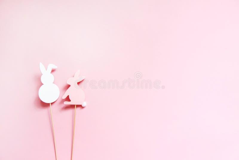 Decoración de la primavera de los conejitos de pascua en los palillos de madera en fondo de papel en colores pastel del rosa suav fotos de archivo libres de regalías