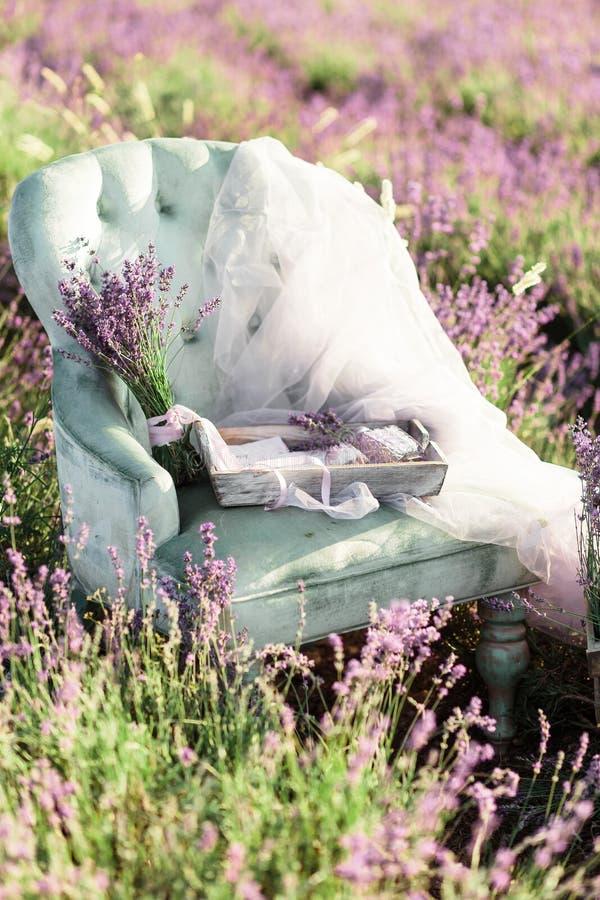 Decoración de la silla en campo de la lavanda del purpur en puesta del sol de oro imágenes de archivo libres de regalías