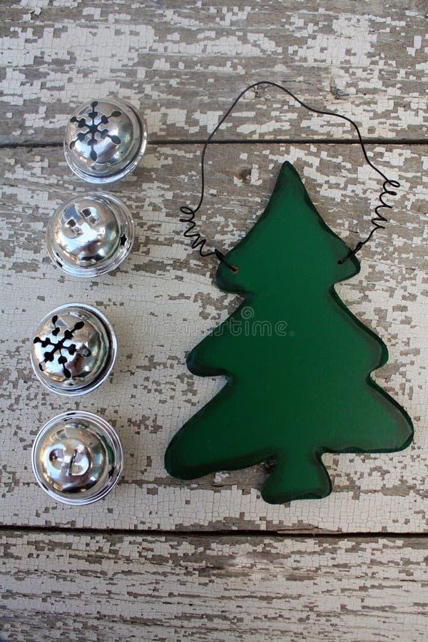 Decoración de madera verde del árbol de navidad en el fondo blanco con cuatro cascabeles imágenes de archivo libres de regalías