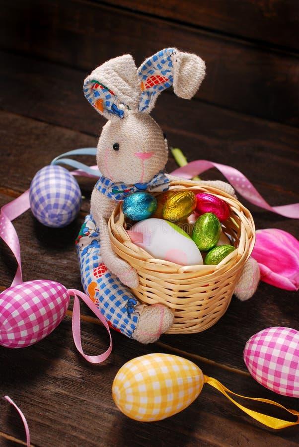 Decoración de Pascua con el conejito que sostiene la cesta y los huevos foto de archivo