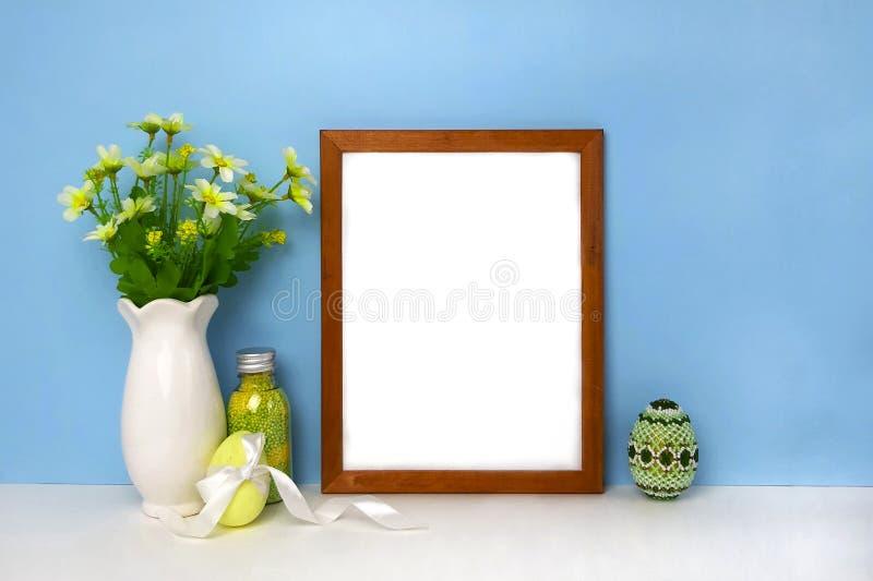 Decoración de Pascua con la maqueta en blanco del marco en la pared azul foto de archivo libre de regalías