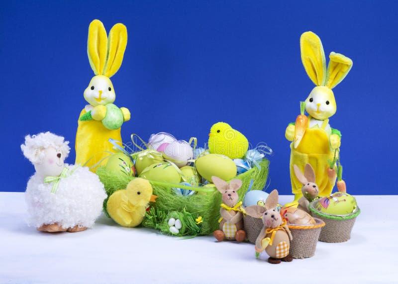 Decoración de Pascua, conejito de pascua amarillo dulce, conejos con el pollo en cesta y los huevos de Pascua, en la tabla blanca imágenes de archivo libres de regalías