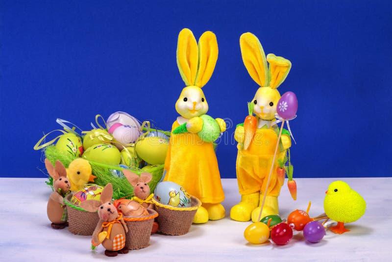 Decoración de Pascua, conejito de pascua amarillo dulce, conejos con el pollo en cesta y los huevos de Pascua, en la tabla blanca fotos de archivo libres de regalías