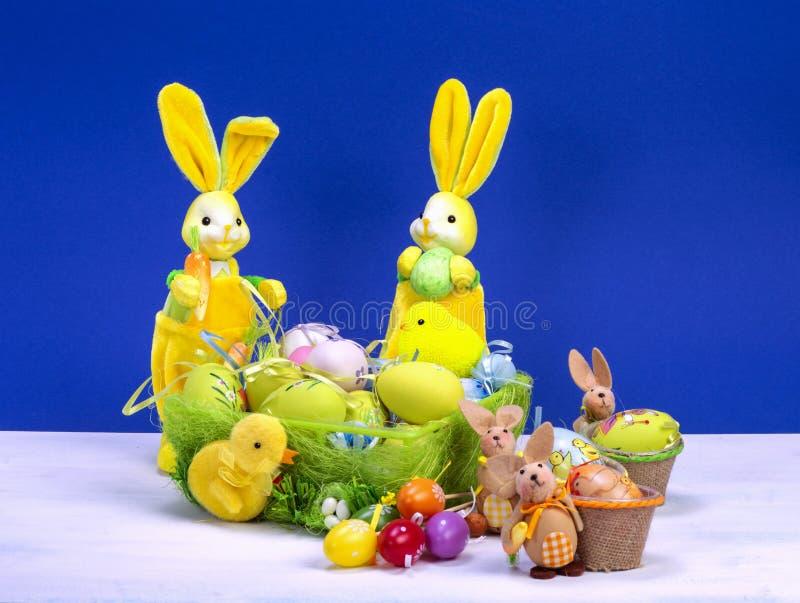 Decoración de Pascua, conejito de pascua amarillo dulce, conejos con el pollo en cesta y los huevos de Pascua, en la tabla blanca imagen de archivo