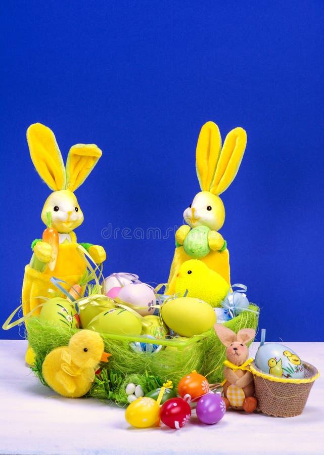 Decoración de Pascua, conejito de pascua amarillo dulce, conejos con el pollo en cesta y los huevos de Pascua, en la tabla blanca fotos de archivo