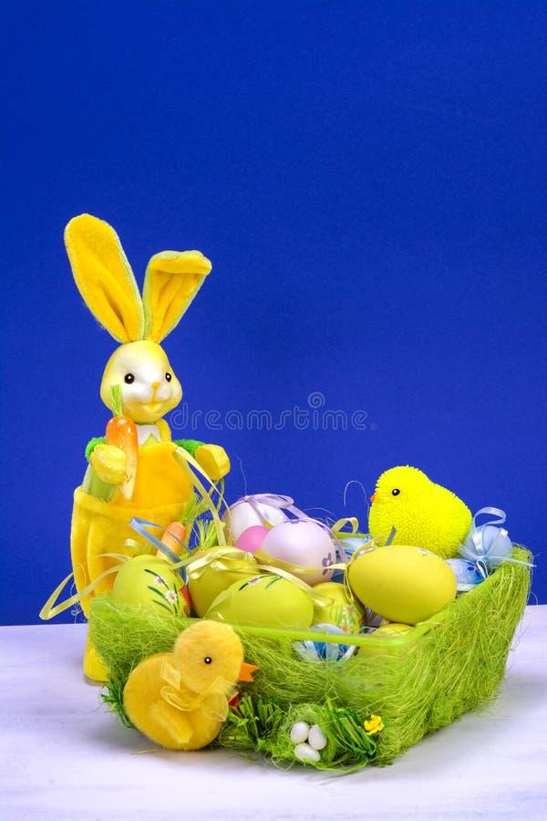 Decoración de Pascua, conejito de pascua amarillo dulce, conejos con el pollo en cesta y los huevos de Pascua, en la tabla blanca foto de archivo