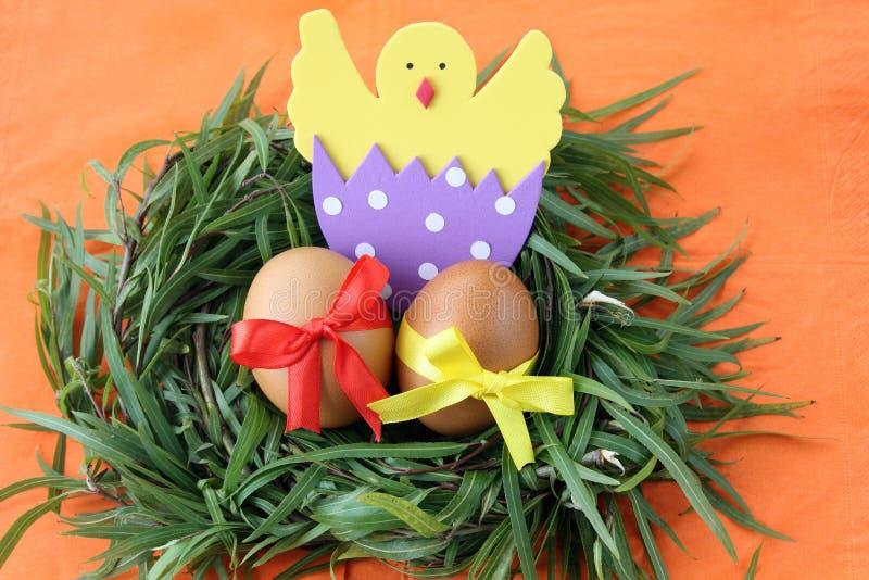 Decoración de Pascua: los huevos amarillos y el pollo tramado hecho a mano en cáscara de huevo en ramitas de la hierba verde jera imagen de archivo