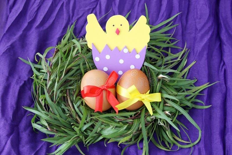 Decoración de Pascua: los huevos amarillos y el pollo tramado hecho a mano en cáscara de huevo en ramitas de la hierba verde jera imagen de archivo libre de regalías
