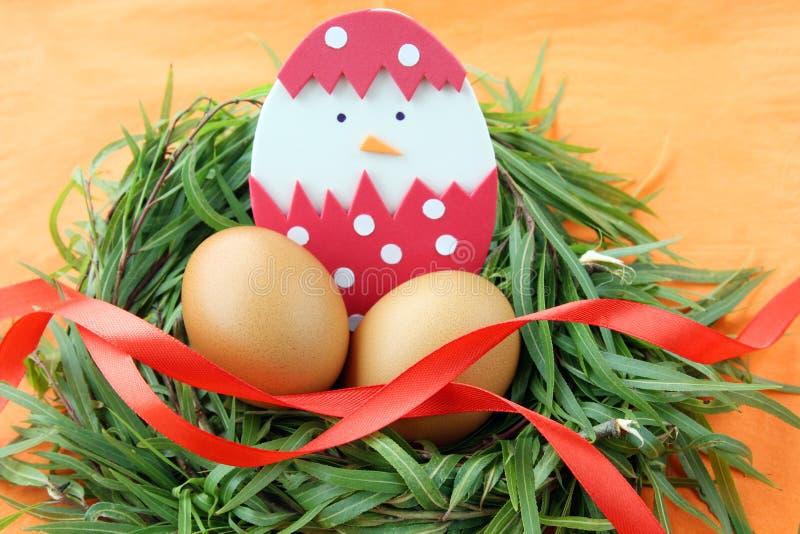 Decoración de Pascua: los huevos amarillos y el pollo tramado hecho a mano en cáscara de huevo en ramitas de la hierba verde jera fotos de archivo