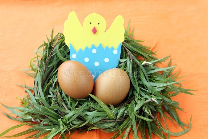 Decoración de Pascua: los huevos amarillos y el pollo tramado hecho a mano en cáscara de huevo en ramitas de la hierba verde jera fotos de archivo libres de regalías