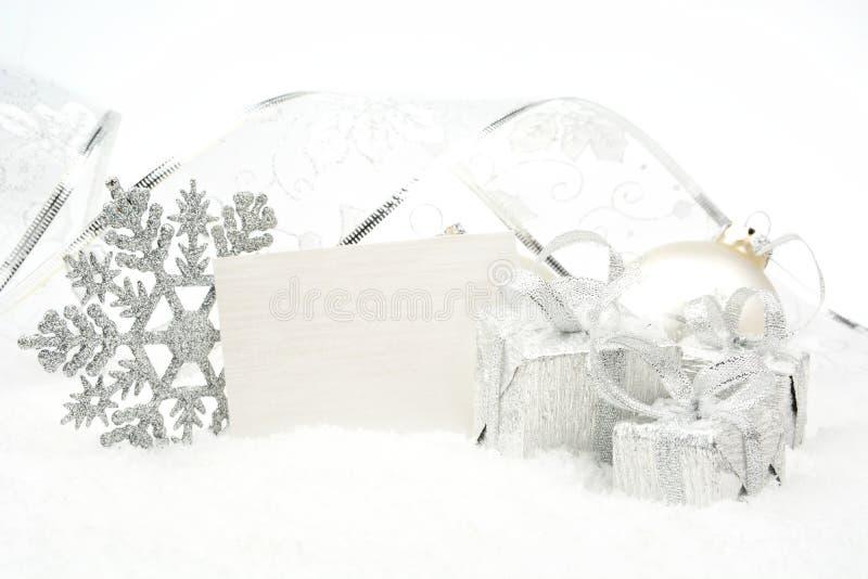 Decoración de plata de la Navidad en nieve con la tarjeta de los deseos imagen de archivo libre de regalías