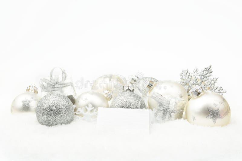 Decoración de plata de la Navidad en nieve con la tarjeta de los deseos fotos de archivo