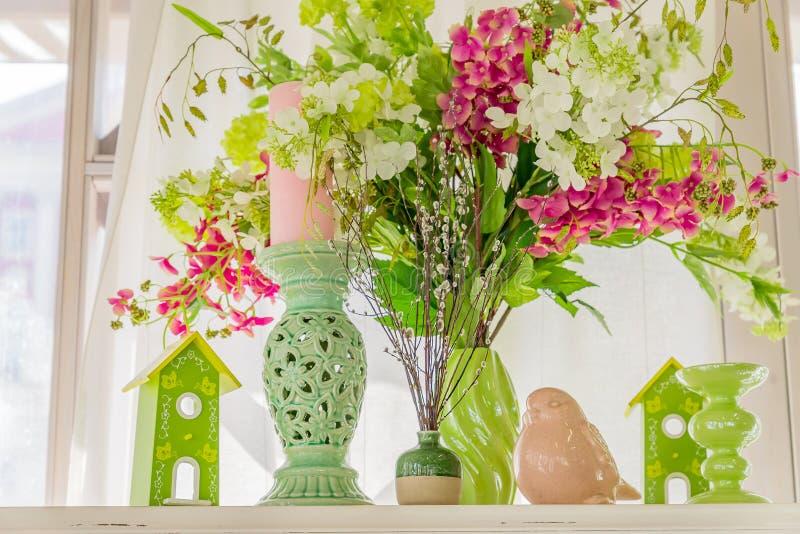 Decoración de primavera en tonos verdes y rosas Flores blancas y rosadas florecientes, estatuilla de pájaro, palos de vela y pája fotos de archivo