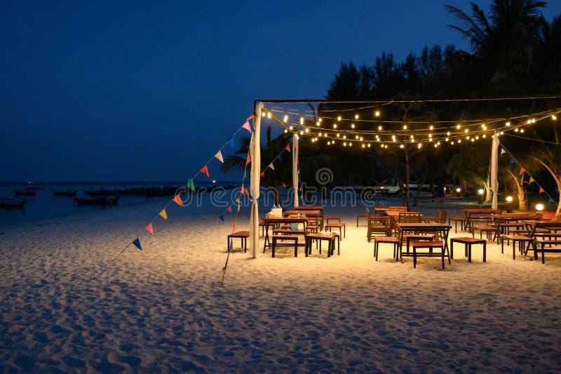 Decoración de sistema de la mesa de comedor con la bandera el brillar intensamente y de los colores de la lámpara en la playa foto de archivo libre de regalías