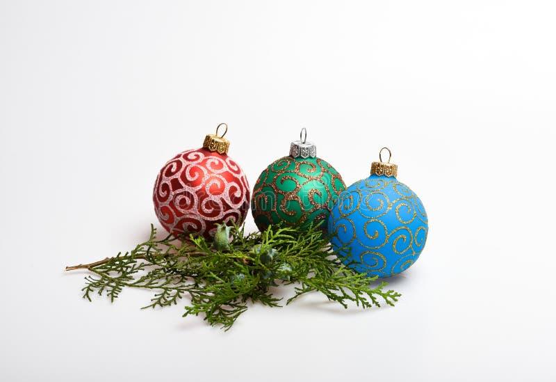 Decoración de tres bolas de la Navidad cerca de la rama del verde del ciprés Concepto de las vacaciones de invierno Adorne el árb imagenes de archivo