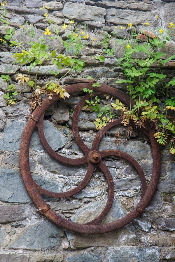 Decoración del jardín con la rueda de madera vieja del carro imagen de archivo