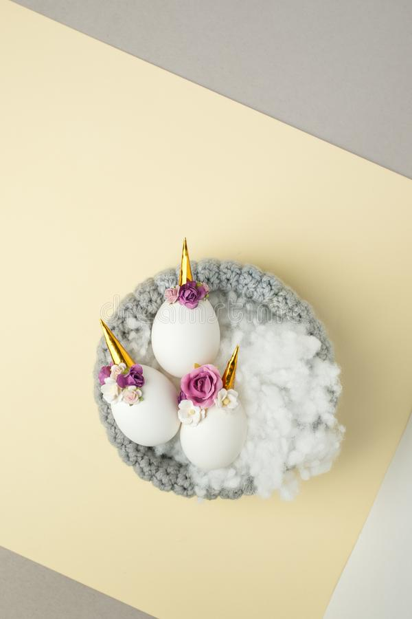 Decoración del unicornio del witn de los huevos de Pascua en la tabla en colores pastel amarilla, tarjeta de felicitación de la p fotos de archivo