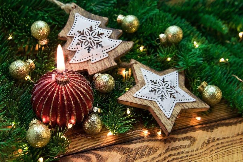 Decoración del vintage de la Navidad con la rama del abeto y la vela roja en primer imagenes de archivo