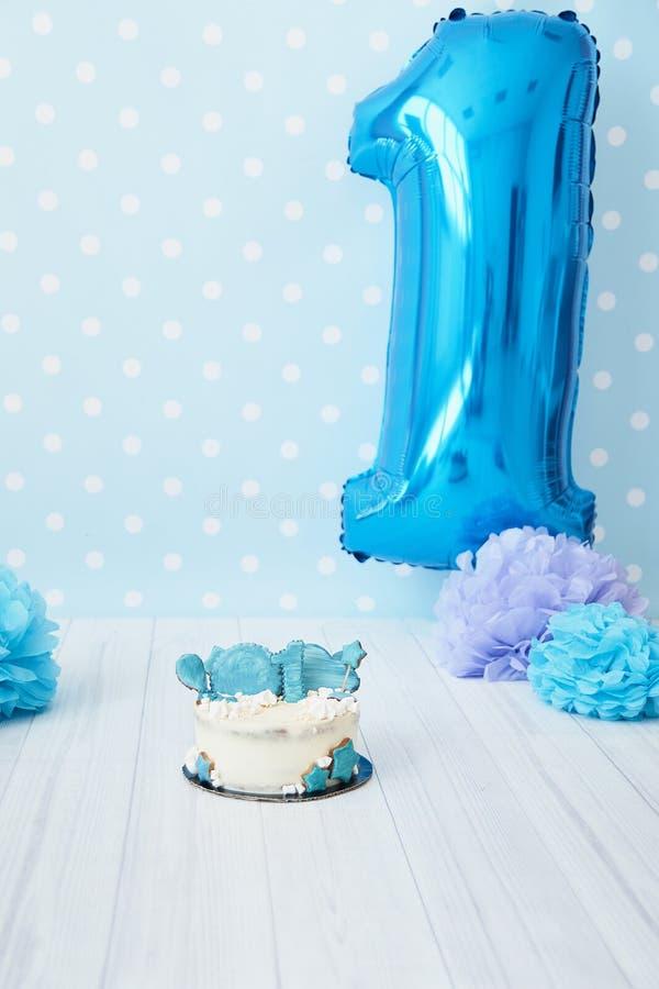 Decoración festiva del fondo para el cumpleaños con la torta, letras que dicen uno y globos azules en estudio, abetos del choque  fotos de archivo libres de regalías