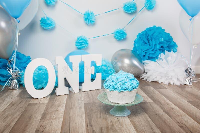 Decoración festiva del fondo para la celebración del cumpleaños con la torta gastrónoma, letras que dicen uno y globos azules en  imagen de archivo libre de regalías