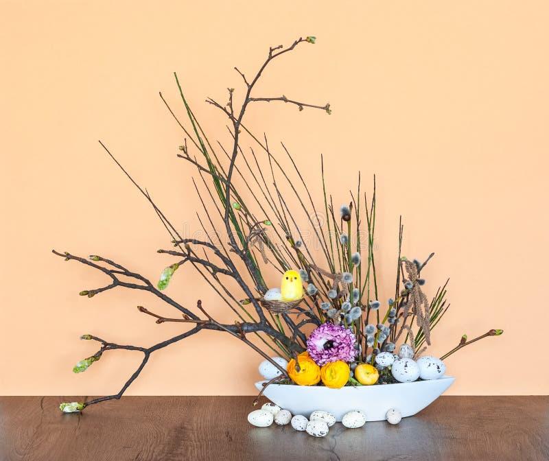 Decoración floral de Primavera-Pascua con las ramitas jovenes, los huevos y un polluelo fotos de archivo