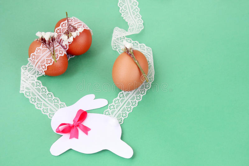 Decoración hecha a mano de Pascua: huevos de Pascua con el cordón blanco y el conejito de papel festivo aislados en fondo verde imagen de archivo libre de regalías