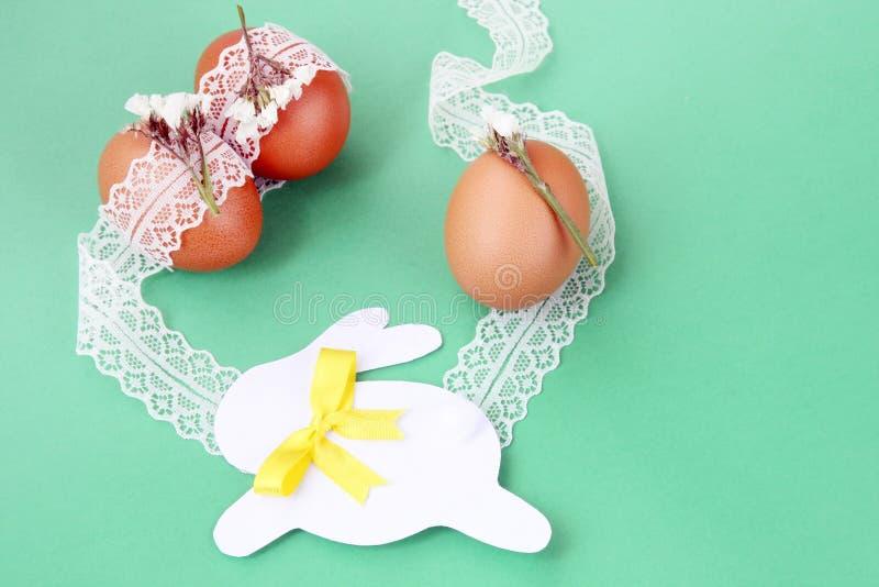 Decoración hecha a mano de Pascua: huevos de Pascua con el cordón blanco y el conejito de papel festivo en fondo verde imagenes de archivo