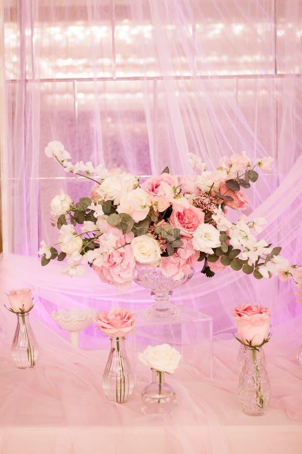 Decoración hermosa con la tela y las flores Un florero grande con las flores blancas y rosadas Pequeños floreros con las rosas fotos de archivo libres de regalías