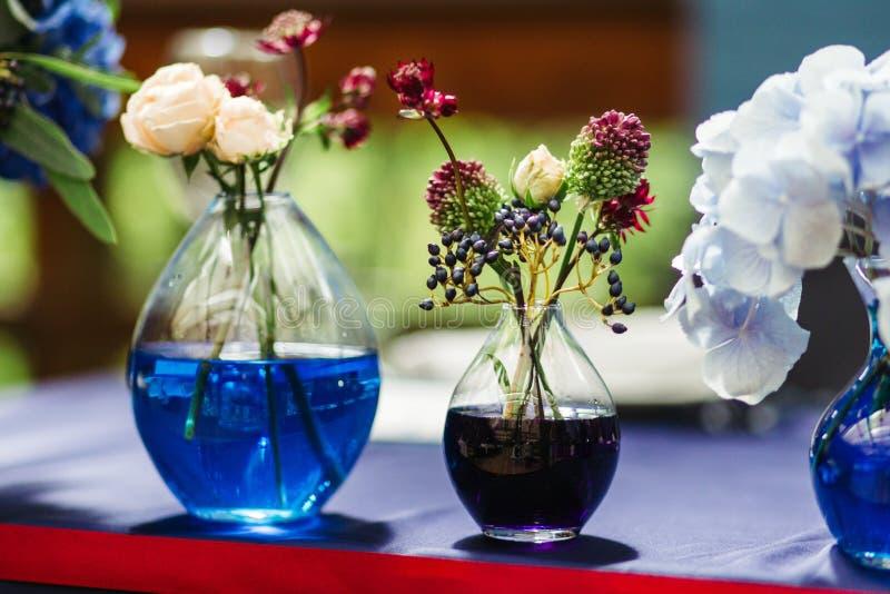 Decoración hermosa en el weddingin Tarros con agua coloreada foto de archivo libre de regalías