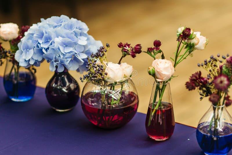 Decoración hermosa en el weddingin Tarros con agua coloreada imagen de archivo