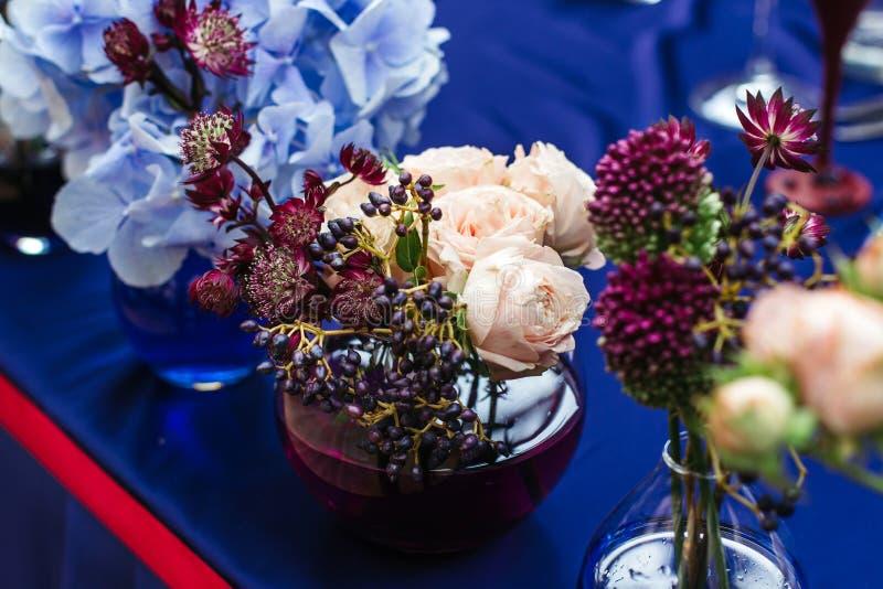 Decoración hermosa en el weddingin Tarros con agua coloreada foto de archivo