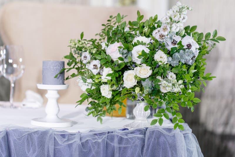 Decoración hermosa y exquisita de la celebración de la boda Banquetee la tabla servida con un mantel azul, placas y imagen de archivo