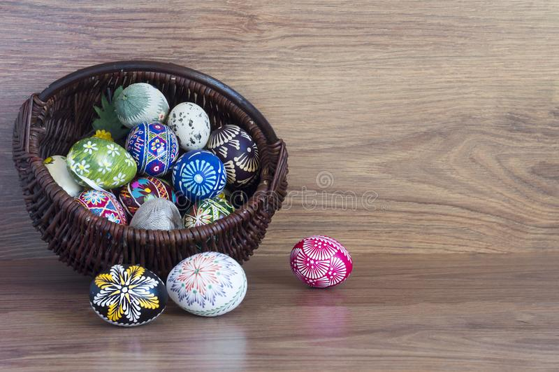 Decoración - huevos del color de Pascua en una cesta fotos de archivo