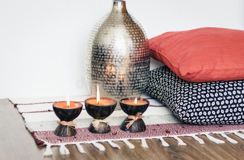 Decoración interior casera acogedora, velas ardientes en cáscara del coco en una manta multicolora con el florero del metal y alm fotografía de archivo libre de regalías