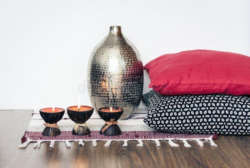 Decoración interior casera acogedora, velas ardientes en cáscara del coco en una manta multicolora con el florero del metal y alm fotos de archivo libres de regalías