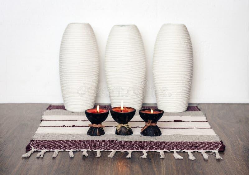 Decoración interior casera acogedora, velas ardientes en cáscara del coco en una manta multicolora con el fondo de cerámica blanc foto de archivo
