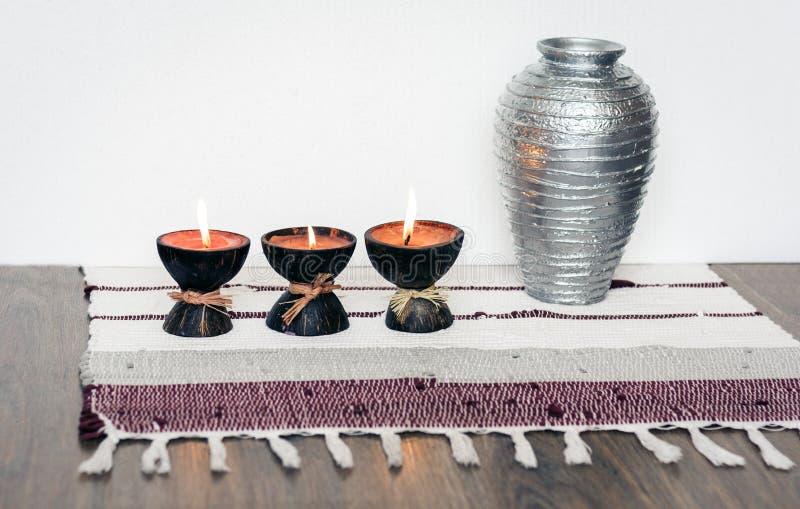 Decoración interior casera acogedora, velas ardientes en cáscara del coco en una manta multicolora con el fondo del florero del m fotos de archivo libres de regalías